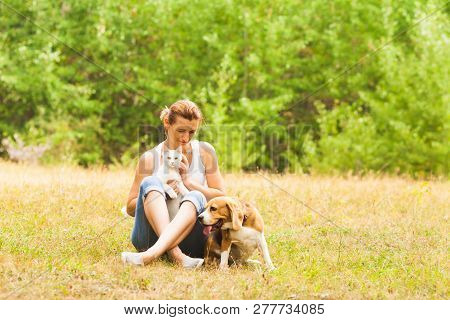 Smiling Woman Sitting On A Grass With Cat And Dog