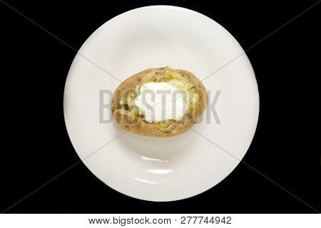 Baked Russet Potato. Hot Baked Russet Potato on a white plate with fresh butter and sour cream. Isolated on black. Room for text.