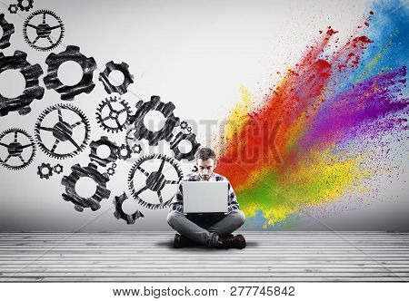 Man Working On Laptop Against An Wall Painted With Engine Gear Wheels And Powder Explosion.