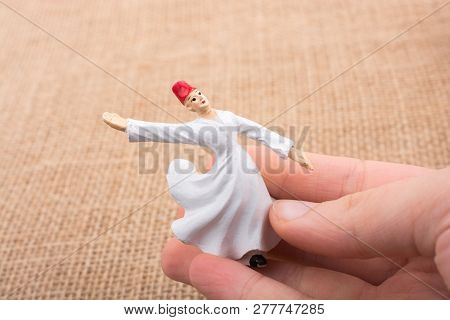 Hand holding a white color Sufi Dervish figurine in hand poster
