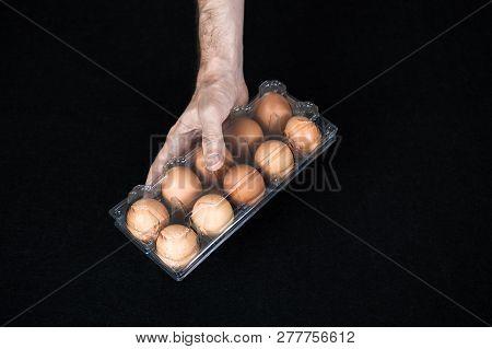 Male Hand Holding A Plastic Egg Box Full Of Hen Eggs On Black Felt Background.