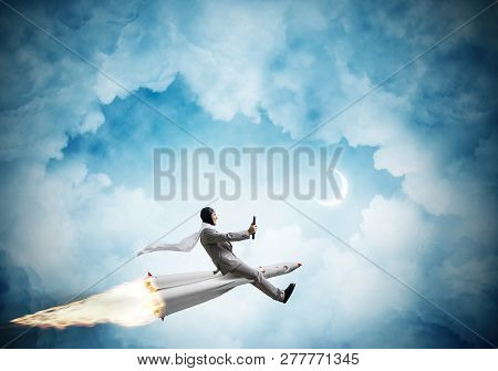 Conceptual Image Of Young Businessman In Suit Flying On Rocket With Blue Night Skyscape With Clouds
