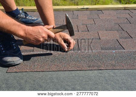 Roofer Installing Asphalt Shingles On House Roofing Construction With Hammer And Nails. Roofing Cons