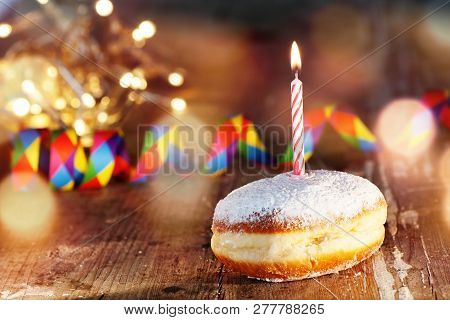 Donut With Candle And Colorful Streamers On Rustic Wood For A Carnival Celebration