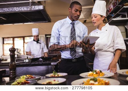 Male manager and female chef using digital tablet in kitchen at hotel