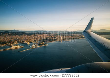 Airplane Wing On The Sky Above Barcelona City At Sunrise, Spain.