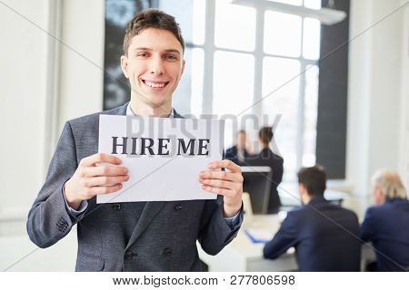 Job candidate holds sign for finding a job
