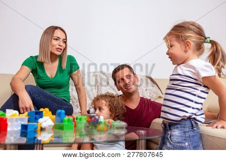 Family Time - Young Parent And Children Playing With Blocks Toys