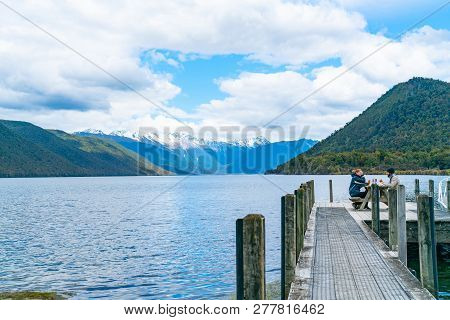 Lake Rotoroa New Zealand - October 6 2018; Couple In Warm Clothing Dining Together On Pier Extending