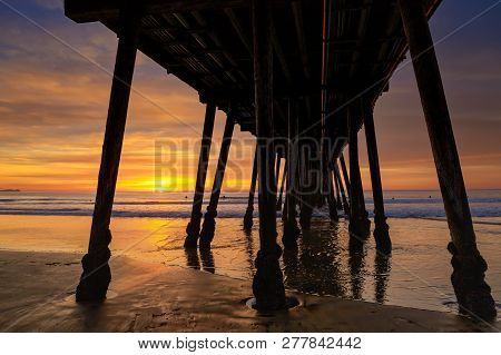 The Setting Sun At The Pier In Imperial Beach, California With The Silhouettes Of Surfers Waiting Fo