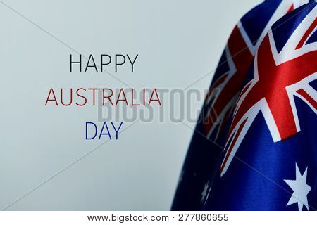 closeup of some australian flags and the text happy australia day against an off-white background