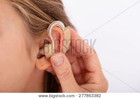 Doctor Inserting Hearing Aid In Girl's Ear