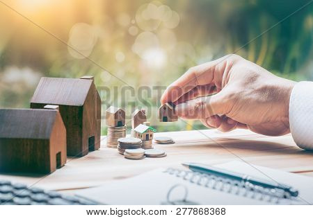 poster of House placed on coins Men's hand is planning savings money of coins to buy a home concept concept for property ladder, mortgage and real estate investment. for saving or investment for a house,