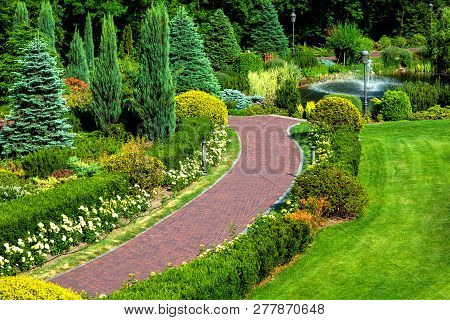 Red Pavement Walkway In The Backyard With Landscape Design And Various Bush Plants And Trees, Top Vi