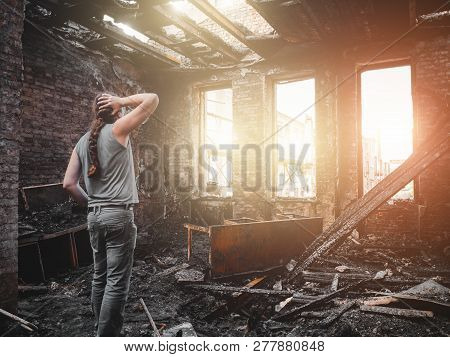 Man House Owner Stands Inside His Burnt House Interior With Burned Furniture In Arson And Holding He