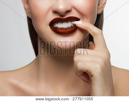 Close-up Portrait Of The Lower Half Of A Woman's Face With A Malicious Grin. He Picks A Long Fingern