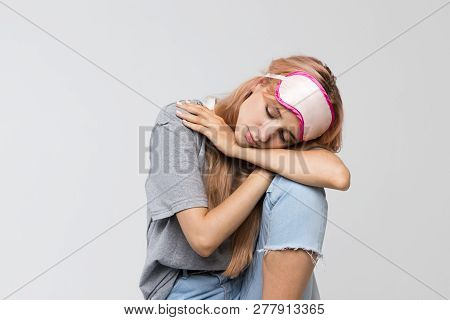 Studio Portrait Of Sleepy Young Woman In Grey T-shirt Feels Tired After Work, Sitting On A Chair And