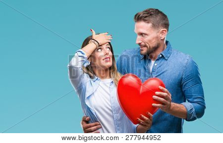Young couple in love holding red heart over isolated background stressed with hand on head, shocked with shame and surprise face, angry and frustrated. Fear and upset for mistake.