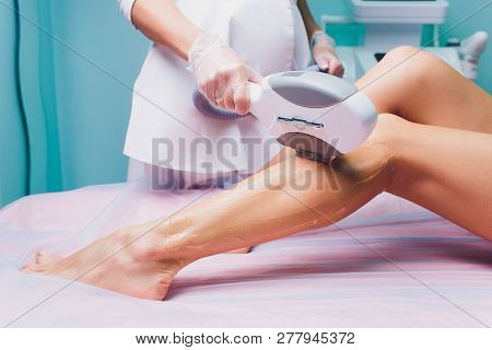 Beautician Removes Hair On Beautiful Female Legs Using A Laser. Hair Removal On The Legs, Laser Proc