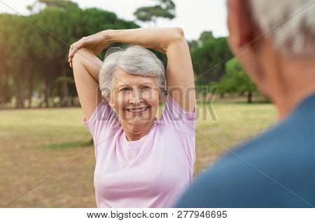 Smiling senior woman looking at man while doing arm stretching exercise. Old man in conversation with wife that is exercising with hand over head. Elderly couple doing fitness exercise at park.