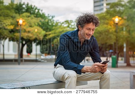 Mature businessman sitting on bench and using smart phone at dusk. Happy smiling guy in smart casual reading a message on cellphone. Stylish man surfing the net with smart phone in the evening.