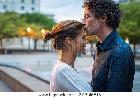 Mature husband kissing wife on forehead in the street in the evening. Romantic senior man giving a kiss to her woman in the city street. Loving middle aged couple in love at dusk.