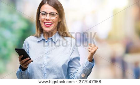 Young beautiful business woman texting message using smartphone over isolated background screaming proud and celebrating victory and success very excited, cheering emotion