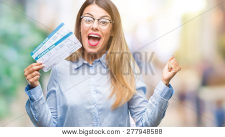 Young beautiful woman holding boarding pass over isolated background screaming proud and celebrating victory and success very excited, cheering emotion