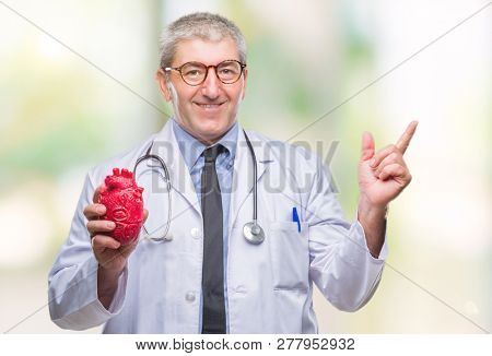 Handsome senior cardiologist doctor man holding heart over isolated background very happy pointing with hand and finger to the side