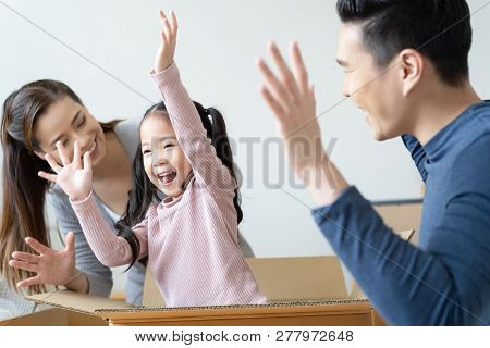 Happy Little Girl Screaming Jumping Out Hiding In Cardboard Box Having Fun With Mom Dad Packing Movi
