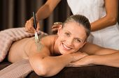 Smiling mature woman looking at camera while beautician getting mud mask on back with brush. Portrait of happy middle aged lady with clay treatment on back. Woman in spa doing clay mask exfoliation. poster