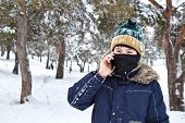 talking on the phone boy in a knitted hat with a bubo and balaclava on a winter walk poster