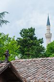 Skopje, Macedonia - June 10, 2013: Catholic wooden cross on top of the roof on foreground and Mustafa Pasha Mosque tower on the background in Skopje, Macedonia poster