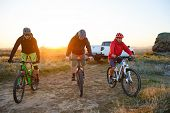 Friends Cyclists Riding Enduro Bikes in the Mountains in front of the Pickup Off Road Truck at Warm Autumn Sunset. MTB Adventure and Car Travel Concept. poster