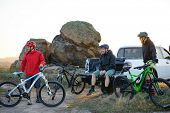 Friends Cyclists Resting near the Pickup Off Road Truck after Enduro Bike Riding in the Mountains at Warm Autumn Sunset. MTB Adventure and Car Travel Concept. poster