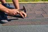 Roofer installing Asphalt Shingles on house Roofing Construction with hammer and nails. Roofing Construction. Roofing Contractor laying Asphalt Shingles roof tiles. poster