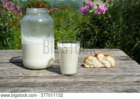 A Two-litre Can Of Milk Stands On A Wooden Table On The Street. Nearby Stands A Faceted Glass Of Mil
