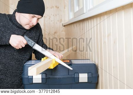 A Man In Black Gloves Holds A Wooden Block On A Tool Box And Cuts It