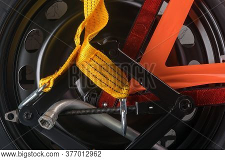 On A Spare Tire For A Car Lies A Yellow Tow Rope And Warning Triangle, Background