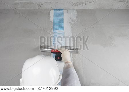 A Repairman In A White Helmet Applies Mortar With A Spatula To The Mesh Glued To The Seam On The Wal