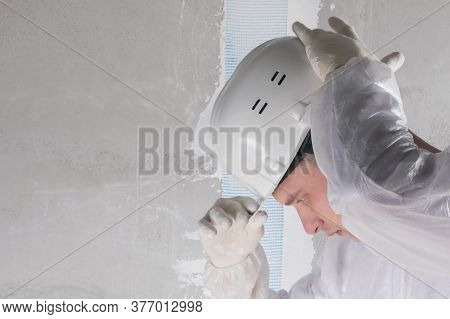 A Worker In A White Suit And Gloves Straightens His Helmet On His Head Against The Background Of The