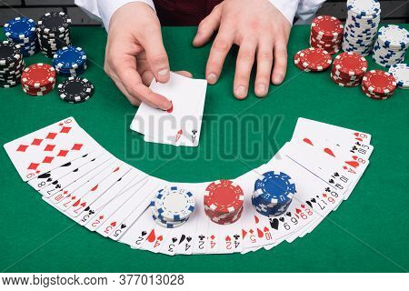 Two Aces In The Hands Of The Dealer On The Background Of The Table With Cards And Chips