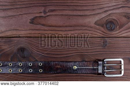 Old Leather Belt With Buckle On An Old Wooden Board With Space For Text. Mens Brown Belt Made Of Gen