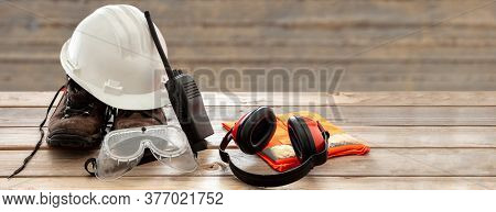 Work Safety Protection Equipment. Industrial Protective Gear On Wooden Table, Blur Construction Site