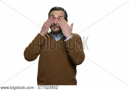 Tired Mature Man Is Rubbing His Eyes. Portrait Of Middle-aged American Man Isolated On White Backgro
