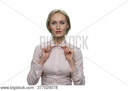 Blond Woman With Narrowed Eyes Holding Her Collar On White Background. Standing Attractive Woman In