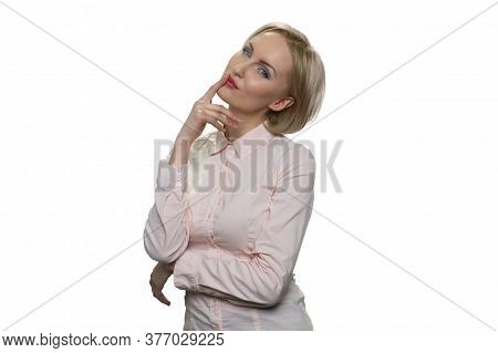 Good-looking, Alluring Woman In White Blouse Holding Her Finger Near Lips And Standing Against White
