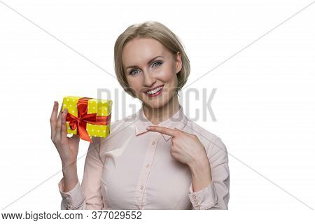 Happy Smiling Blond Woman Poiting At Gift In Her Hand. Portrait Of Cheerful Impressive Blonde Woman