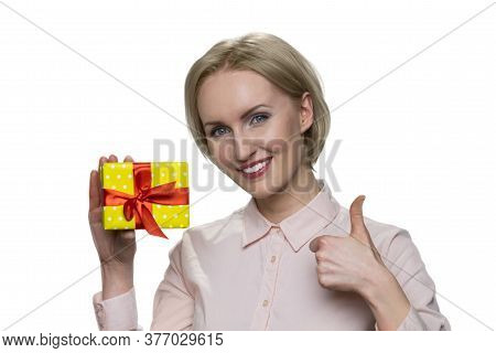 Happy Smiling Blond Woman Holding Gift Box And Making Ok Gesture. Portrait Of Cheerful Impressive Bl
