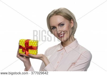 Positive Blonde Woman Holding Little Gift Box With Happy Face Smiling On White Background. Cheerful